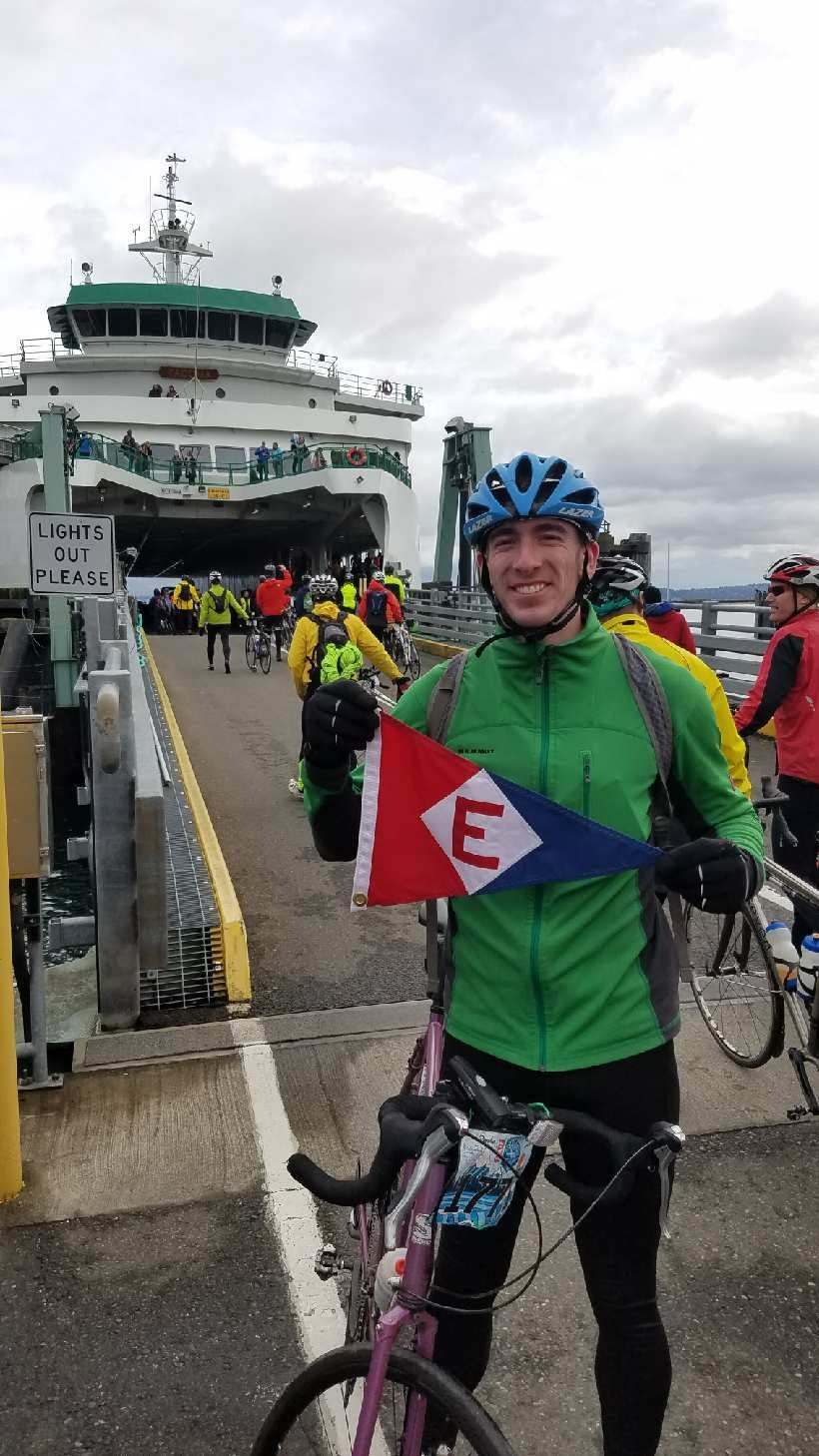 Langdon Junge takes his EYC burgee on the Chilly Hilly bike race on Bainbridge Island, WA.