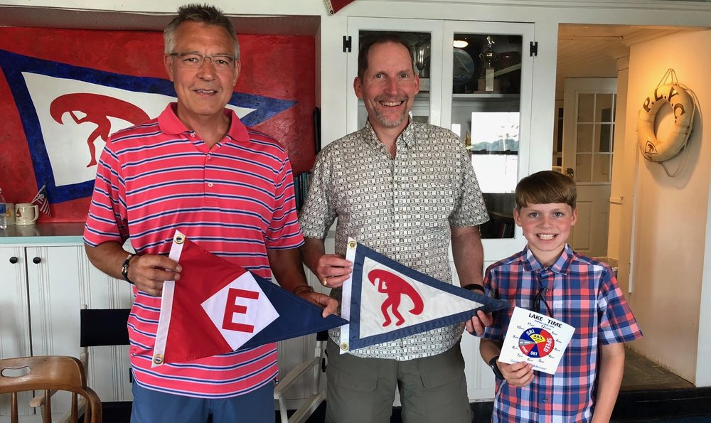Eric DeFreest (center) and son Nicolai exchange burgees with the Commodore of the Portage Lake Yacht Club in Akron, OH.