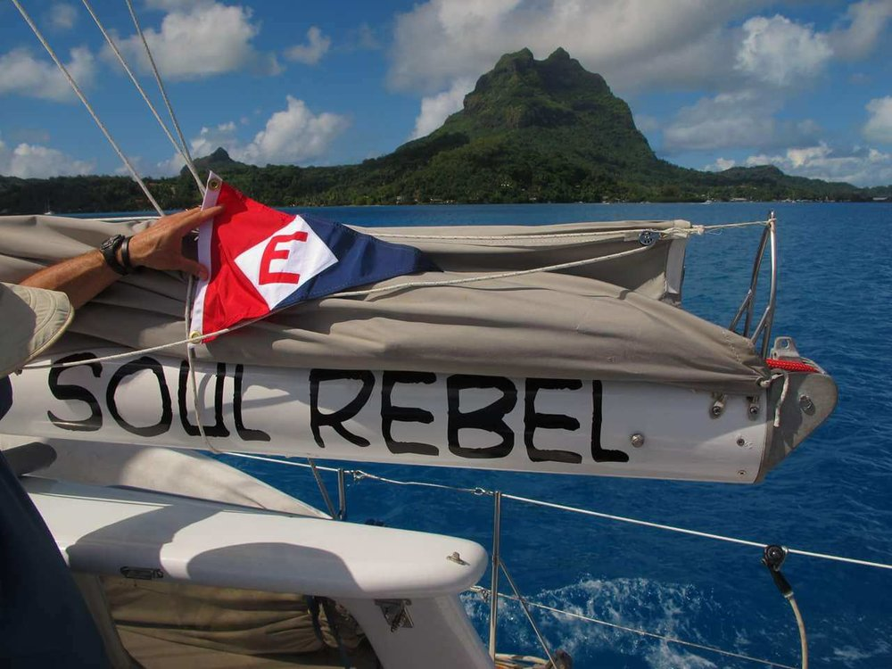 Roger Bailey hoists the colors in Bora Bora on his retirement cruise