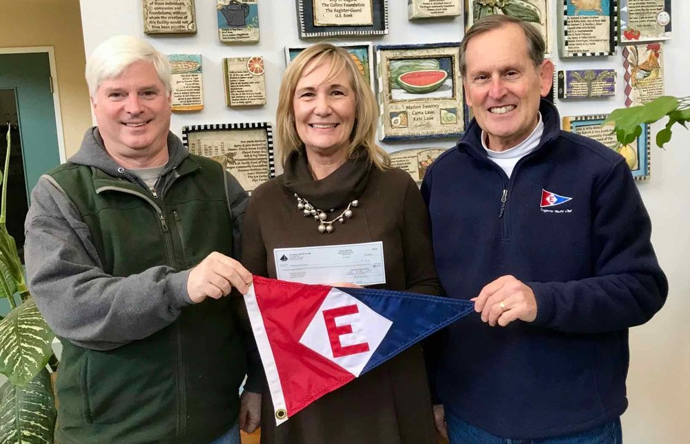 Club Manager Rich Aaring (left) and Rear Commodore Gary Powell (right) present a check and the EYC burgee to Food for Lane County's Executive Director Beverlee Potter