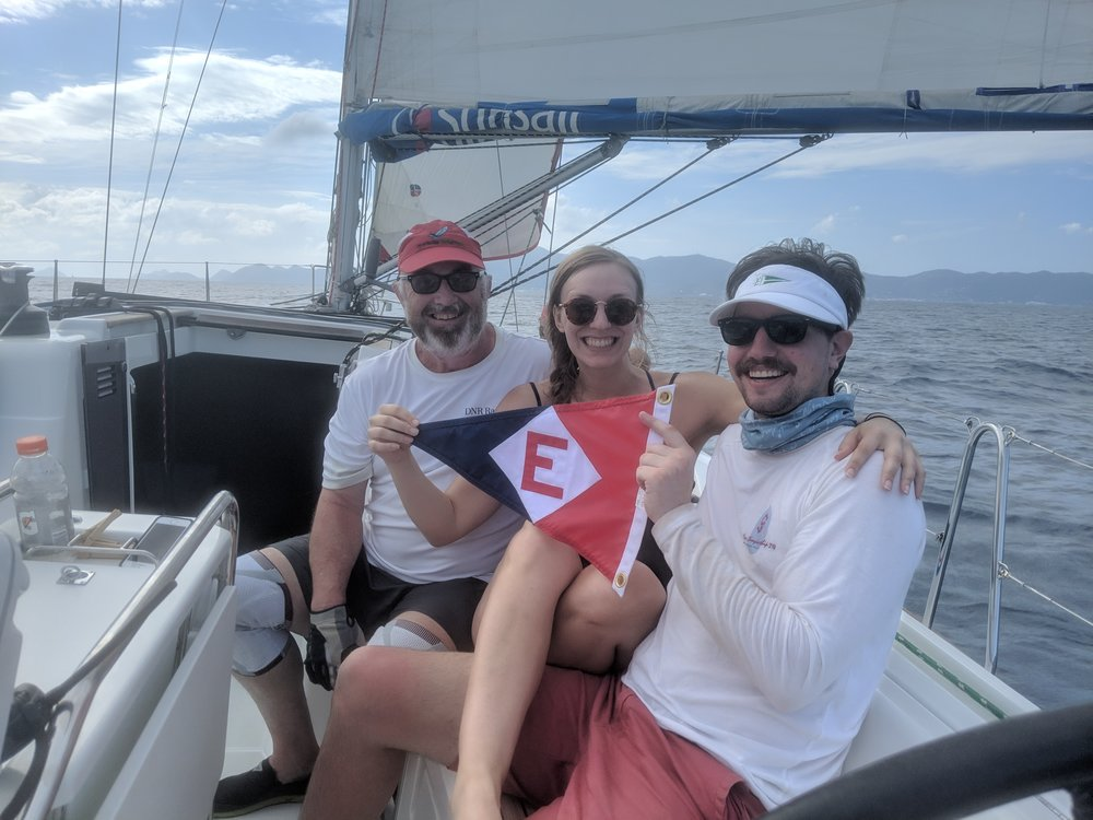 Chris Thomas, Kimi Schler, and Jac Thomas, members of the DNR Racing team, take a moment from training for the Spring Regatta in the British Virgin Islands to hoist the EYC burgee