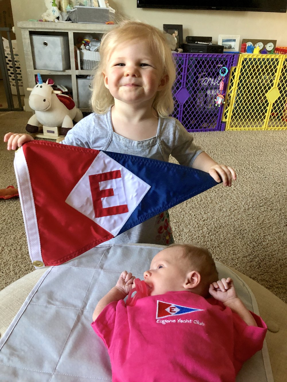 Zoey shows off her EYC burgee and her new little sister Natalie at home in Cottage Grove, Oregon.