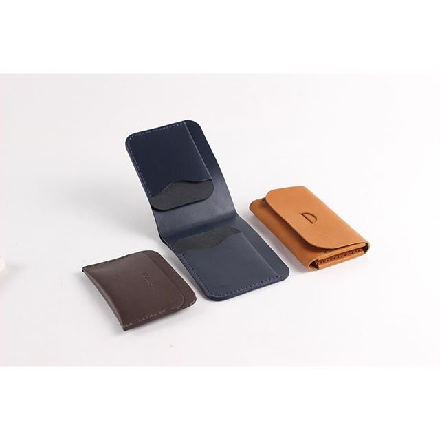A crowd of IEFrancis kangaroo leather wallets. Three Pocket in dark brown, Landscape Fold in navy, and a Tab in terracotta.  All carefully designed and handmade in Melbourne ❤️
