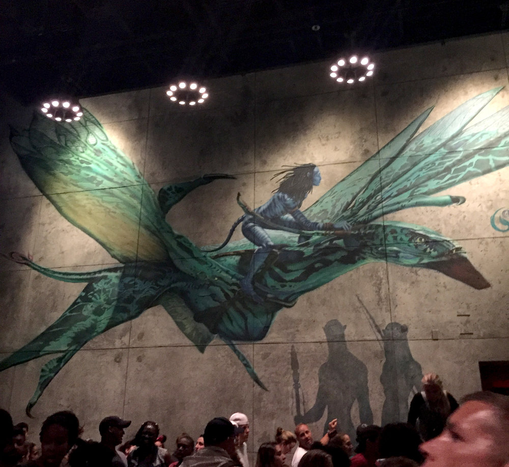 The last section of the queue for the Flight of Passage winds through a large room with a life-sized mural of an Avatar riding a banshee.