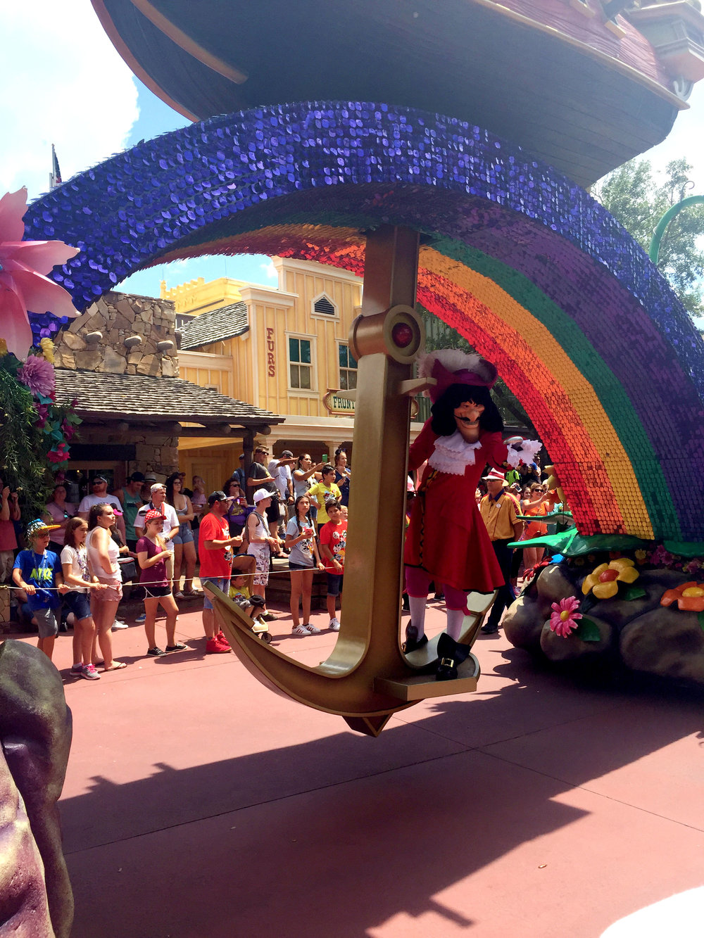 Captain Hook swings from a giant anchor under the shimmering, mosaic covered rainbow.