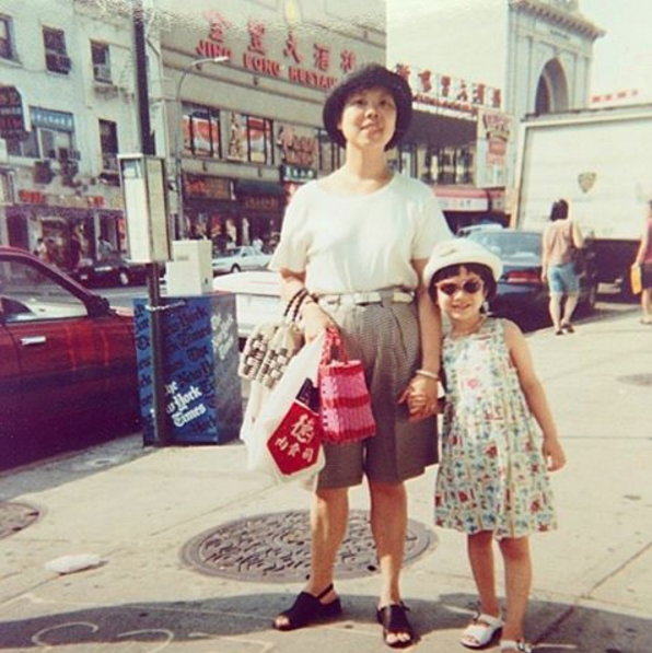 My mother and five-year-old me posing together on the Bowery in Chinatown. My father probably took this picture after my mother and I did some hard bargaining at the fruit and veggie stands.