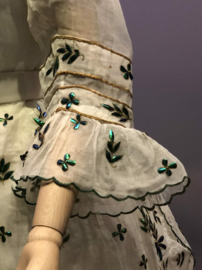 An unnatural use of nature - muslin dress adorned by beetle wings. Muslin day dress decorated with beetle wing cases, 1868-9, Britain.© Victoria and Albert Museum, London.
