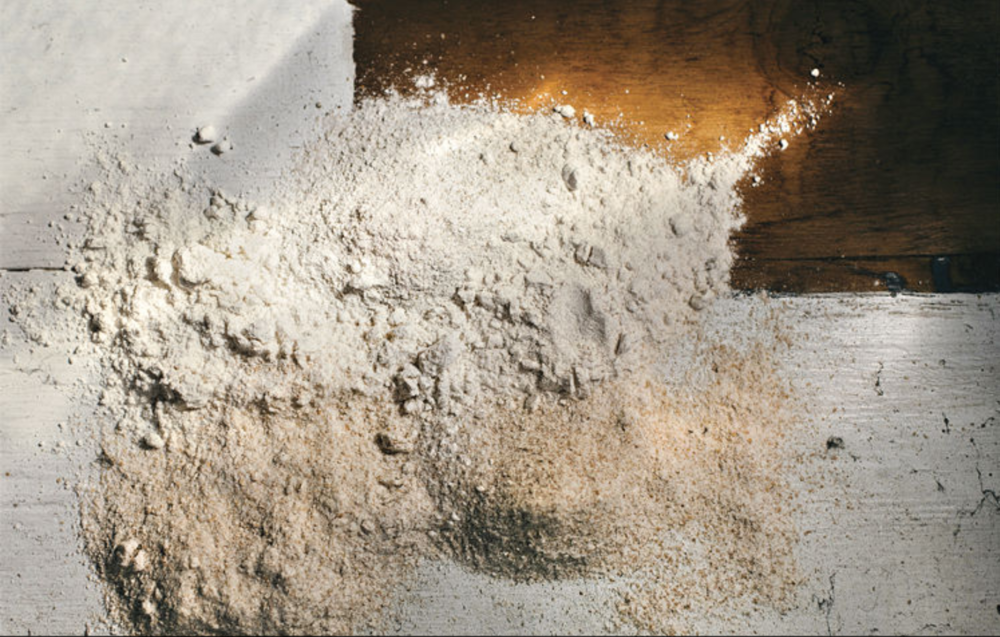 "Unlike a bag of white all-purpose flour you buy at the grocery store, The Mill's flours vary in color, from grayish-blue rye and rosy Turkey Red to light brown Glenn bread flour.  ""They're not the same product,"" Brockman-Cummings says of most industrially milled flours. ""There's no flavor from their flour. It's a medium, whereas ours is a medium with flavor and nutrition.""  All of the flours produced at The Mill are whole-kernel, which means the nutrition in the bran and germ – including oils, vitamins, proteins, amino acids and minerals – are left intact. This is achieved with those Danish Engsko stone mills; most large industrial mills use high-speed roller mills, which process out the bran and germ.  ""The fat and flavor lie in the bran and the germ of the kernel, and largely in the germ,"" Halloran says. ""That germ is not reintegrated in a supermarket product because it has short shelf life, it's very volatile and you want stability. To have true stone milling increases flavor tremendously, regardless of the characteristics of the grain itself.""   Photo by Judd Demaline, of five of the many certified organic flours stone-ground by Jill Brockman-Cummings at The Mill at Janie's Farm, each with a different color, texture, and taste profile. Clockwise from left: Calumet Bread Flour, Wabash Artisan Bread Flour, Whole-Kernel Rye Flour, Des Plaines Pastry/Cake Flour, and Mackinaw flour from the heirloom Turkey Red wheat"