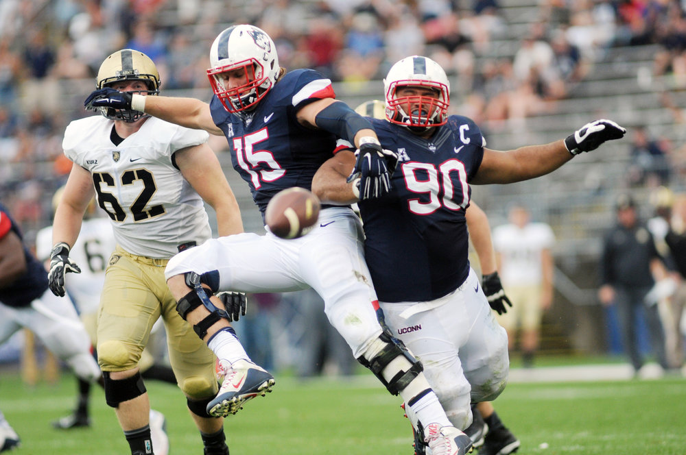 Linebacker Luke Carrezola (15) and defensive lineman Julian Campenni (90) clash for the ball at Pratt & Whitney's Rentschler Field in Hartford, Conn. against Army on Sept. 12, 2015.