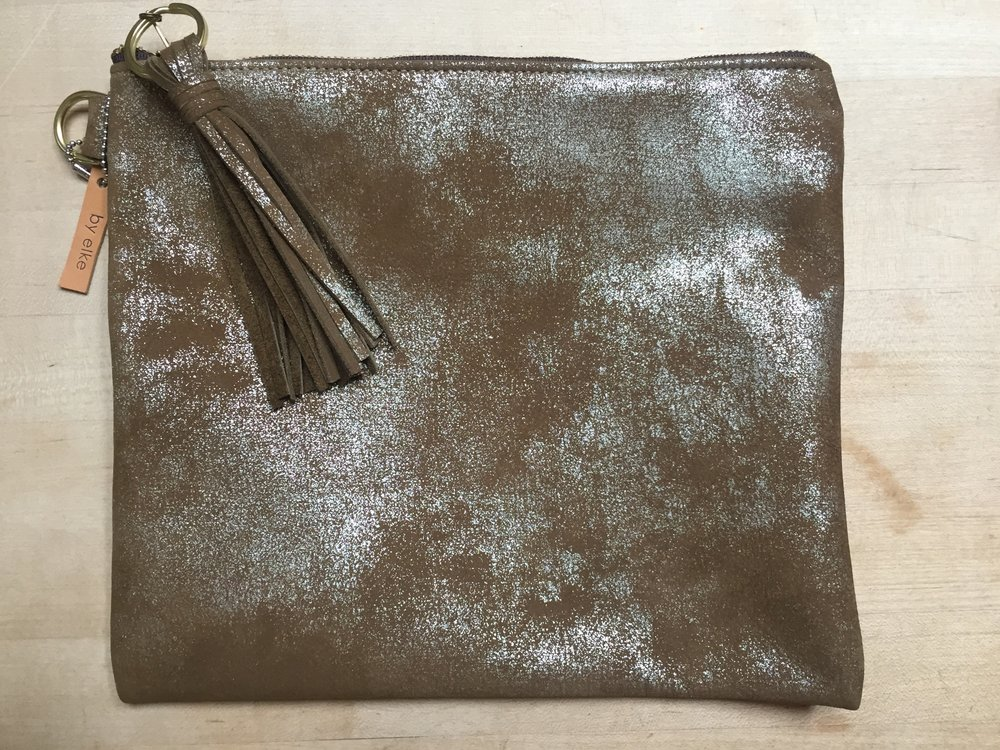Metallic Leather Foldover Clutch by elke - Handmade clutch by elke, a local Boulder company. Clutch made of distressed metallic leather with leather tassel pull.Donor: Elke BergeronItem available for pickup at end of event.Opening bid: $100    Value: $140