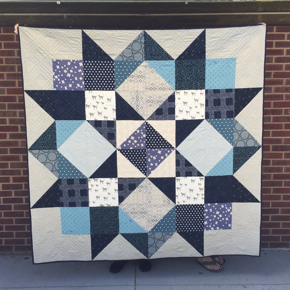 "Large Handmade Quilt, local - This large handmade quilt (72""x72"") is the creation of local artisan, Mary Van Zale. Navy, cream, gray, and blue on Cotton and Steel fabric pieces were assembled to create a warm and cuddly lap quilt. The interior is cotton batting, making the quilt durable for daily use or display.Donor: Mary Van ZaleItem available for pickup at end of event.Opening Bid: $485    Value: $650"