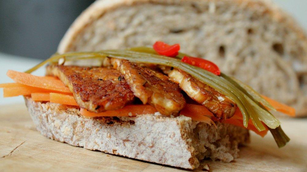 Svež kruh iz kislega testa, kisana pikantna zelenjava in mariniran tempeh.