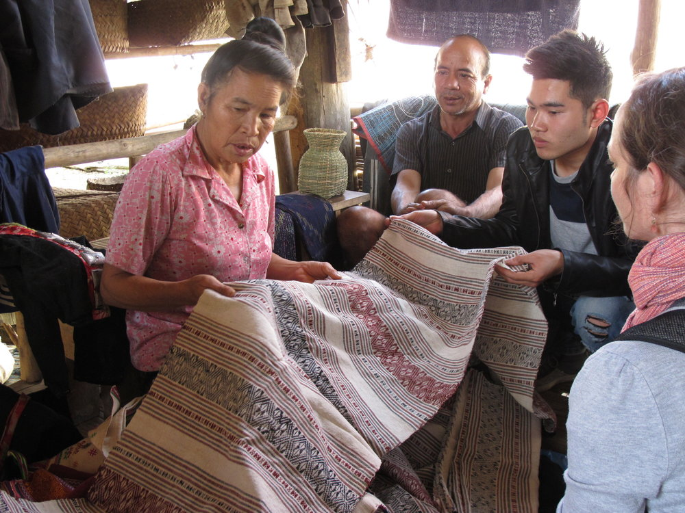 Padee showing us her hand woven textiles with her husband, our guide and translator Sin, and me looking on (Thabou, Laos, January 2016).
