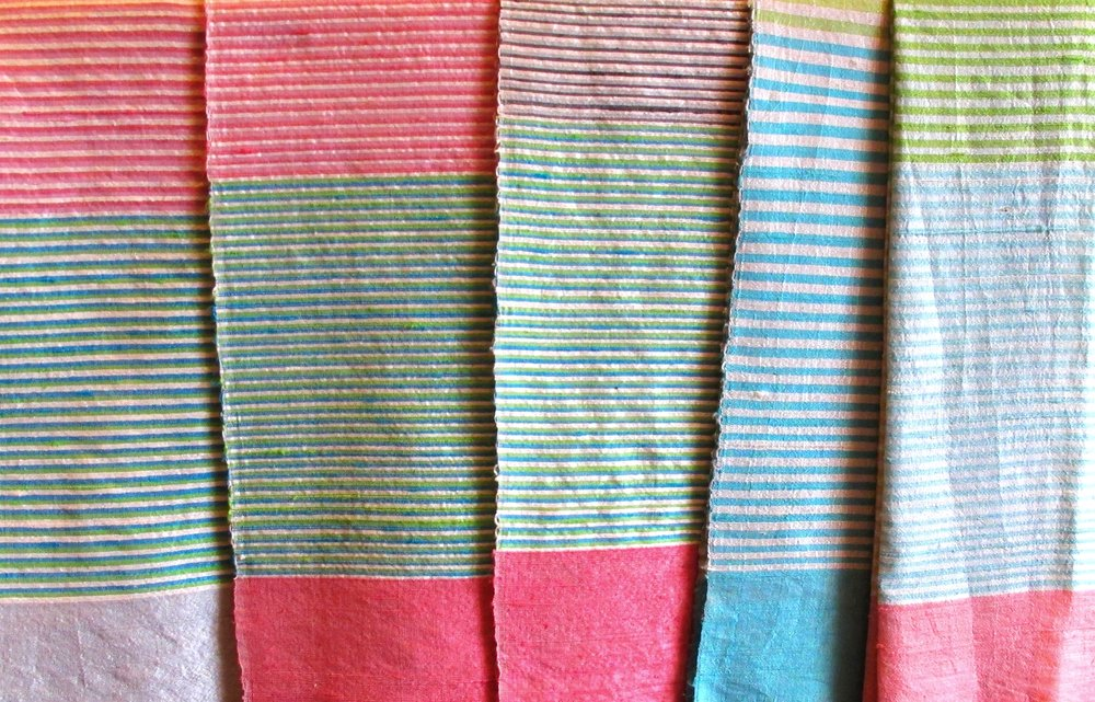 Striped colors of ruby magenta, sky blue and inchworm green among the inviting handcrafted silk scarves of Colors of Life, Phnom Penh, Cambodia