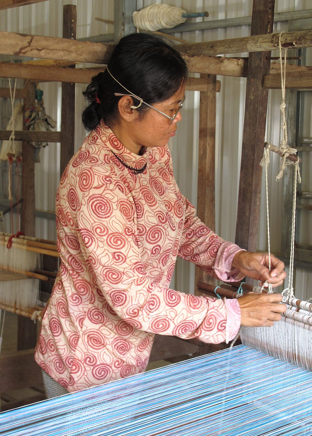 Adjusting the threads of her loom with an eye for perfection, the lead weaver at the Colors for Life workshop in Krang Phnong village, Cambodia