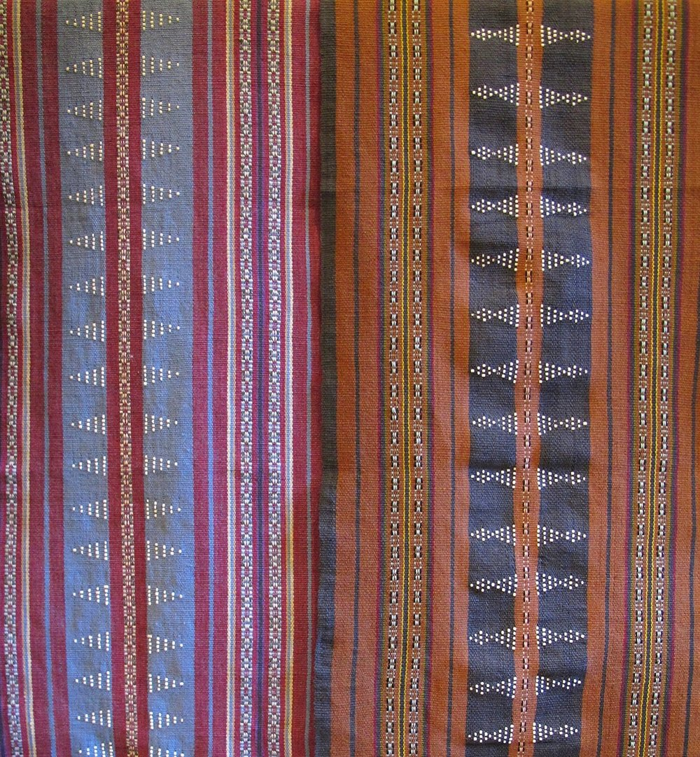 [Earthy warm tones in a fine striped pattern, tiny white beads nested as diamonds, staccato to the touch against a thick tight weave textile. Inviting table runners handwoven by women of the Katu ethnic group in Salavan Provence, Laos. Curated by Ma Te Sai, a lovely fair trade boutique and social enterprise working closely with artisans in Laos.]