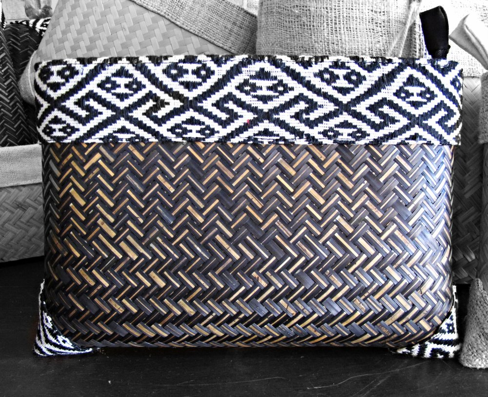 [Fishbone bamboo weave and I wonder how it was made with alternating light dark. Following the weave of the hemp patterned trim and my curiosity wanders, wondering whose artisan hands crafted this, her name and about her life. Bamboo clutch handcrafted by women of the Tai Lao ethnic group, Phonsong Village. Curated by Ma Te Sai.]