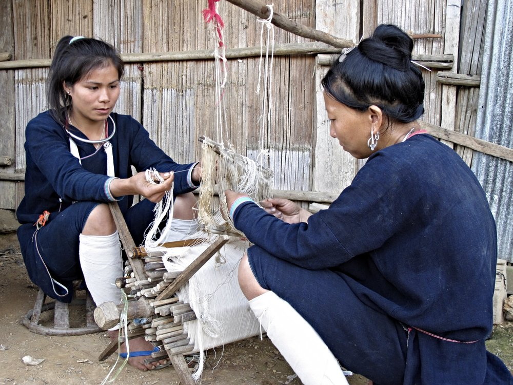 Living in remote mountain villages in Northern Laos, the Lanten ethnic group make and wear distinctive black indigo-dyed cotton clothing. Here women are meticulously preparing the threads of a handloom for weaving.