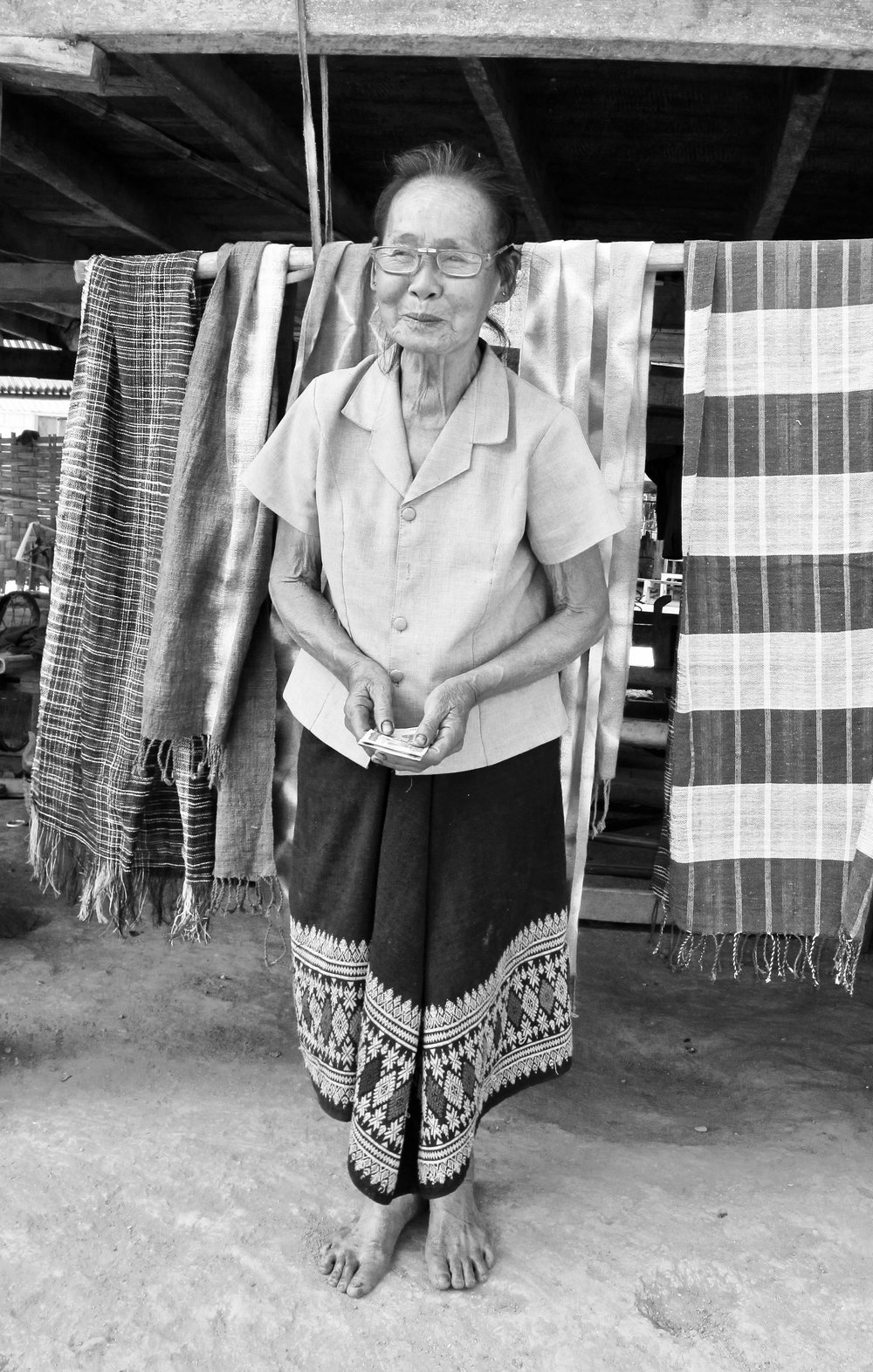 Savong in front her display of scarves. She's one of many weavers in Nayang Tai, a weaving village in northern Laos, who learned from an early age how to spin and weave.