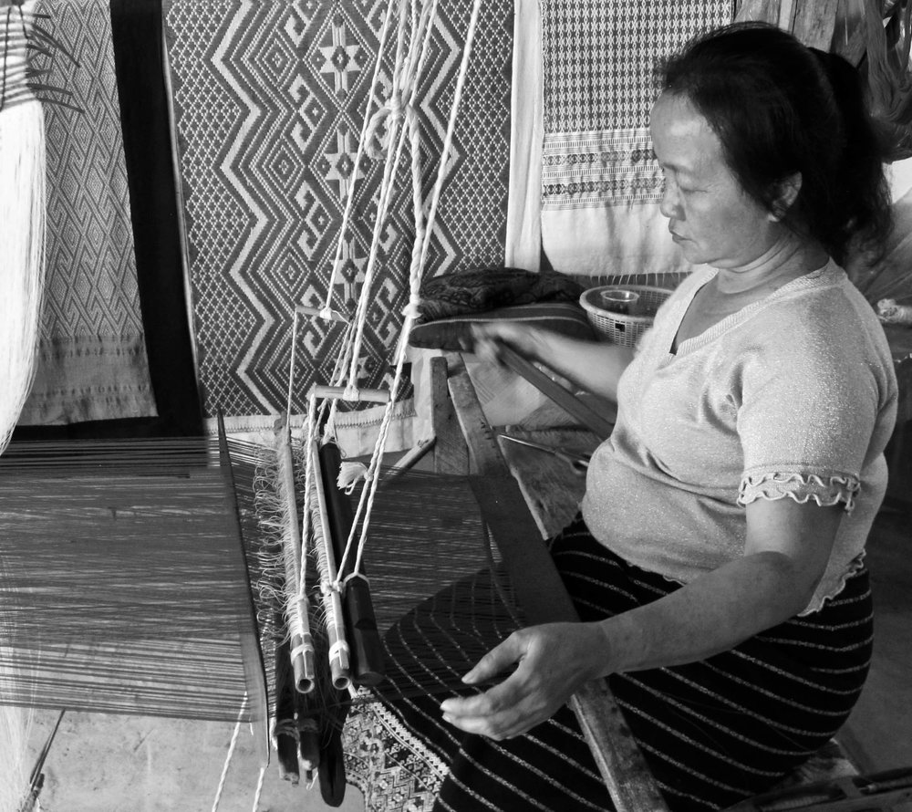 """Her shop was before all the rest in Ban Xangkhong, the famed weaving and paper village just outside of Luang Prabang. She was at her floor loom and welcomed me in, proceeding to show me everything, telling me this and that as I nodded and smiled.  I spoke no Lao, and she no English, but somehow there seemed to be an understanding. She was proud to show me her textiles, indicating she did it all, beautiful designs hanging from floor to ceiling, and neatly stacked on tables.  Her handmade cotton scarves, this one of a simple design and milky misty indigo, caught my attention.I fell in love with it.  Google Translate did help after awhile, at least from English to Lao, but frustratingly not yet available from Lao to English. Calculators are also good at communicating, at least when cost and negotiation comes into play. Her one English word was """"lucky', as she tapped the Lao Kip I gave her on the other textiles """"lucky, lucky, lucky"""" like a mantra.  I stayed for a while afterward, she continued to talk with me, showing me family pictures at this point of her only daughter, and offering me a cold drink.  She wrote down her name in Lao, only to see her name in English on a sign outside her home.  It was a great afternoon. Lucky, lucky, lucky to have met her."""