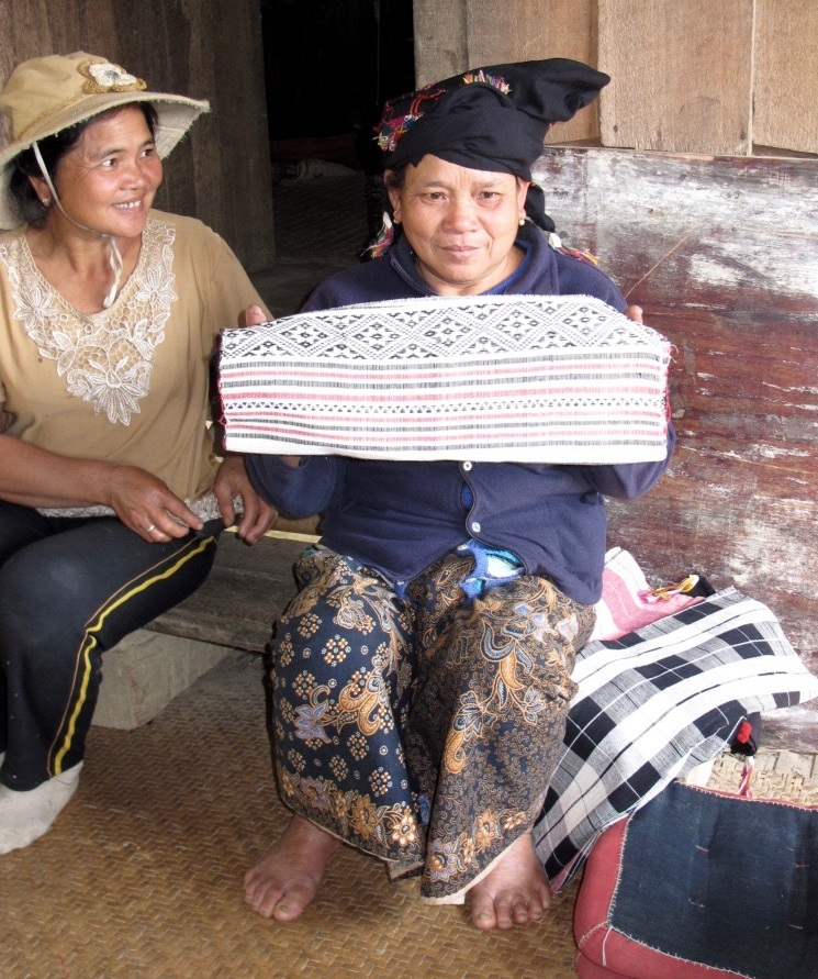 """February 2016 - Excerpt from  """"  Letting Serendipity lead to a weaving village in Laos """" on our blog, The Handmade Chronicle:  Next we walked down the road to a cluster of traditional wooden homes built on stilts to Lasoy's sister's house. Pavan and her husband welcomed us warmly and showed us her collection of cotton textiles she had also handspun, hand dyed, and hand woven. She had products ready to sell.  Inquiring more about the textiles, the cotton was grown from nearby farms, as was the raw silk (we visited the silkworms in various stages of production at another woman's house).  The designs were traditional, referencing the diamond-shaped mahoy seed. The dyes are natural, produced in the village from the indigo plant and macbau, a small fruit plant used for the red.  A little negotiating and I bought two pieces that I could envision as table runners. Pavan seemed most grateful for the sale, eyes watery and her palms pressed together, thumbs touching her forehead, saying  khob chai  to us, """"thank you."""" We learned after that her health was not good and the money would help her get treatment."""