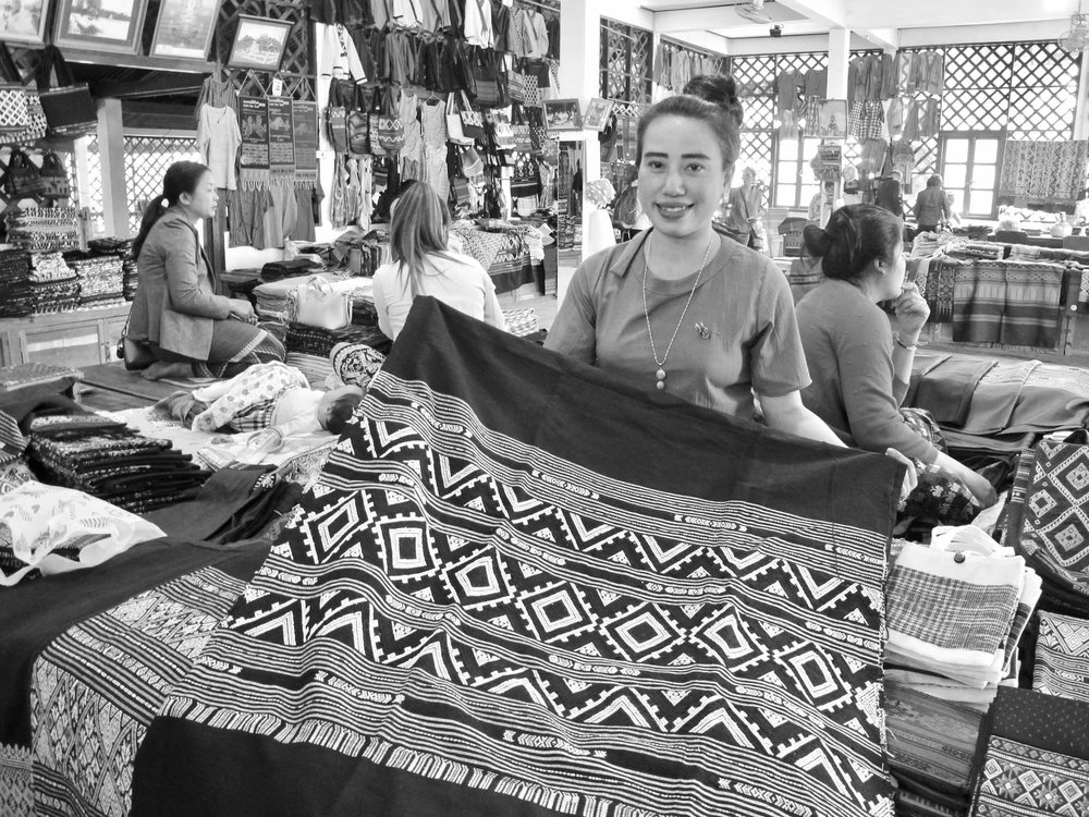 February 2018 – Ban Phanôm, Luang Prabang, Laos – I think she remembered me, showing me her intricately designed textiles, as if she knew I'd like them. She was right. I loved them and bought from her last year. Phonesanit (or Nith, her nickname) is a master Tai Lue weaver, and I have come to appreciate her fine, well-crafted designs and natural colors. It was heartwarming to see her a year later again, and for her to recognize me, too. Here she is with her beautiful diamond field design in black.