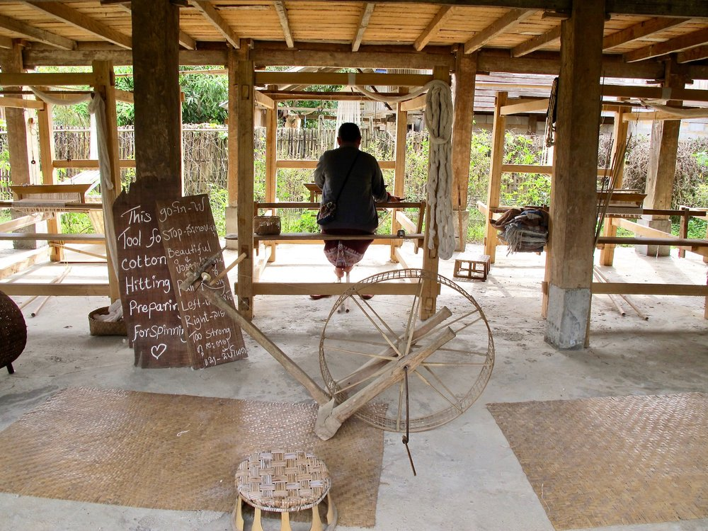Bokai, one of the master weavers, at a loom in the open learning space under the main house.