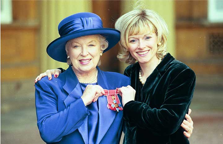 Receiving her OBE with daughter Suzy