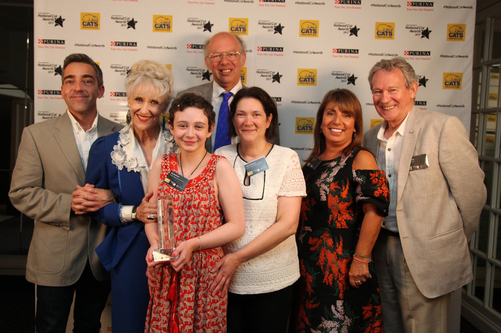 12 year old Evie, centre, with mum Tina, in white, and some of the celebrity judges who presented the award to her