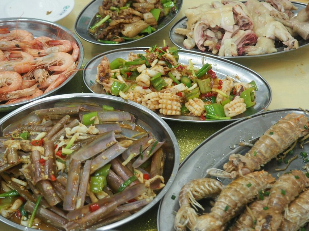 Meaty spread: (clockwise from top right) Boiled whole chicken, languistine, razor shell clams, boiled shrimp, sauteed calimari (center)