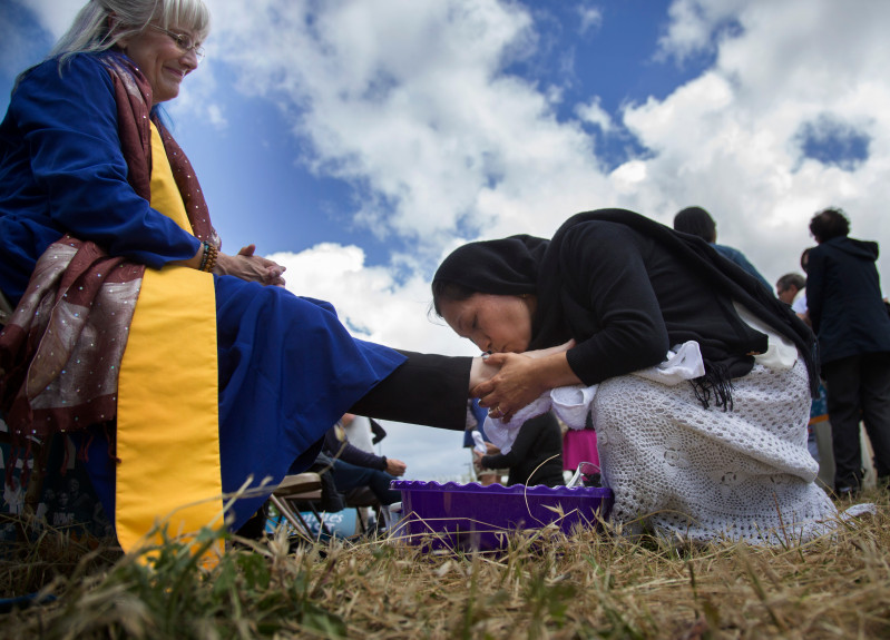 Minerva Rosas, of San Jose, kisses the foot of Rev. Nancy Palmer Jones as local activists wash the feet of immigrants and refugees and they return the favor on Holy Thursday outside the Immigration and Customs Enforcement facility in Morgan Hill, Calif., Thursday, April 13, 2017. PACT, which organized the event, said it is doing it to denounce the administration's recent ICE raids and deportations. (Patrick Tehan/Bay Area News Group)