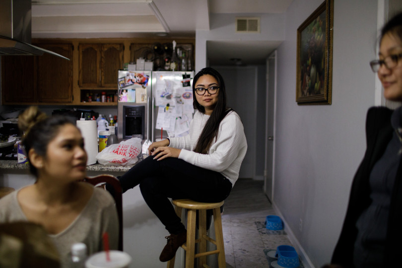 """Jessica Page, center, spends an evening with her relatives, some of whom she shares the home with, on Dec. 21, 2017 in their Milpitas home. Page shares a house in Milpitas with four relatives and wonders if she will be able to afford her own apartment in the coming years. A college graduate and fully employed, she is saving up for graduate school, but feels """"stuck"""" in her living situation because of the high cost of Bay Area housing. (Dai Sugano/Bay Area News Group)"""