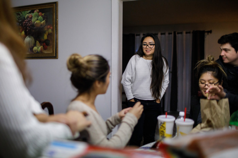 "Jessica Page, center, spends an evening with her relatives, some of whom she shares the home with, and a guest, Kevin Imbesi, far right, on Dec. 21, 2017 in their Milpitas home. Page shares a house in Milpitas with four relatives and wonders if she will be able to afford her own apartment in the coming years. A college graduate and fully employed, she is saving up for graduate school, but feels ""stuck"" in her living situation because of the high cost of Bay Area housing. (Dai Sugano/Bay Area News Group)"