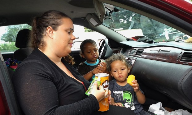 Jennifer Parker feeds snacks to her sons,Tristen, 4, center, and Amarion, 2, right, in their car in Gilroy, Calif., on Monday, August 14, 2017. Jennifer and Ashante Parker couldn't make rent on their Modesto apartment after Ashante suffered an injury to his back. They have lived out of their car for the past few months with their three young children. (Gary Reyes/ Bay Area News Group)