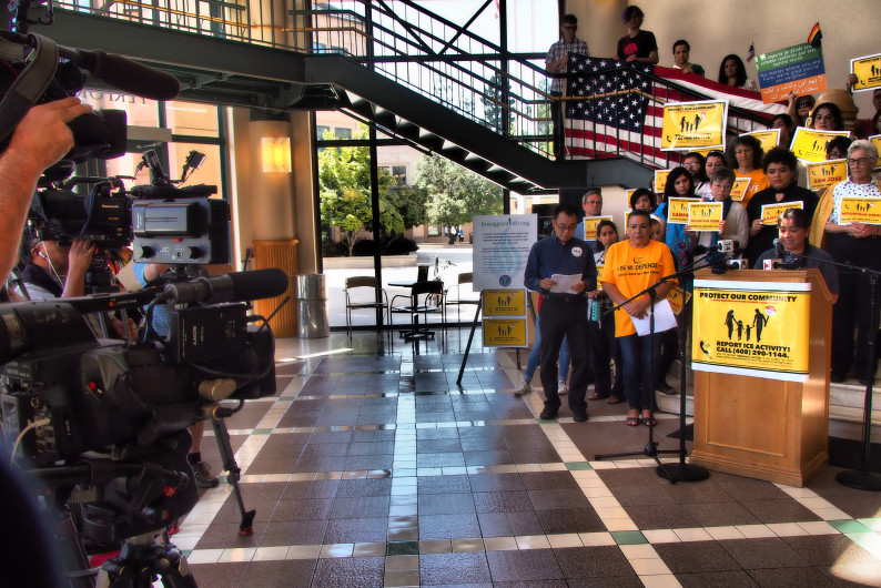 """A phalanx of TV news camera, left, records speechs on Aug. 30, 2017, at Mountain View City Hall, as the Rapid Response Network is launched to help people encountering immigration problems. The posters read, """"Posters read, Protect our community. Report ICE activity! Call 408-290-1144."""" (Shonda Ranson / City of Mountain View)"""