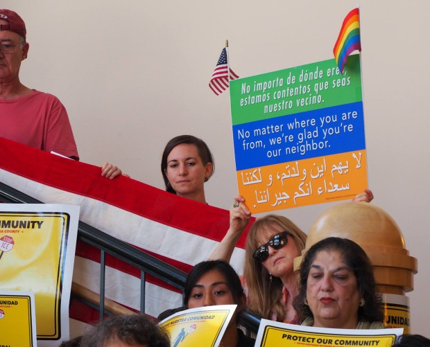 Supporters hold an American flag and posters on Aug. 30, 2017, at Mountain View City Hall, as the Rapid Response Network is launched to help people encountering immigration problems. (Shonda Ranson / City of Mountain View)