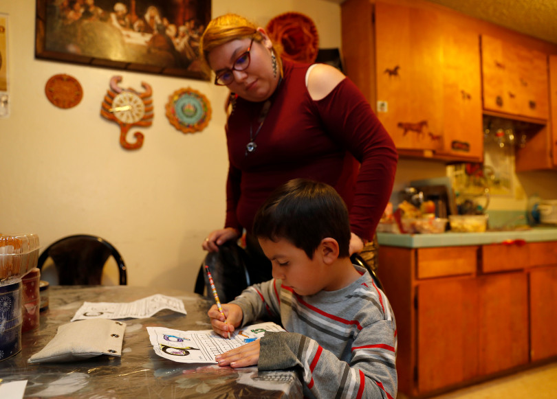 Mountain View, CA - DECEMBER 4: Rocio Carrillo checks on her son Johnatan Flores Carrillo, 5, as he works on his kindergarten homework in their apartment on W. Middlefield Rd. in Mountain View, Calif., on Tuesday, Dec. 4, 2018. Mountain View city officials are considering a developer's proposal to raze 20 rent-controlled, affordable apartments and replace them with 15 new, luxury town houses. (Nhat V. Meyer/Bay Area News Group)