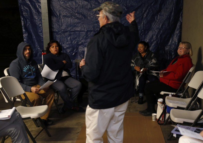 Mountain View, CA – DECEMBER 3: Philip Cosby, a parishioner with Saint Athanasius Church, leads a meeting of residents in a carport at their rent controlled apartment building along Rock St. in Mountain View, Calif., on Monday, Dec. 3, 2018. They meet every week. Mountain View city officials are considering a developer's proposal to raze 20 rent-controlled, affordable apartments and replace them with 15 new, luxury town houses. (Nhat V. Meyer/Bay Area News Group)