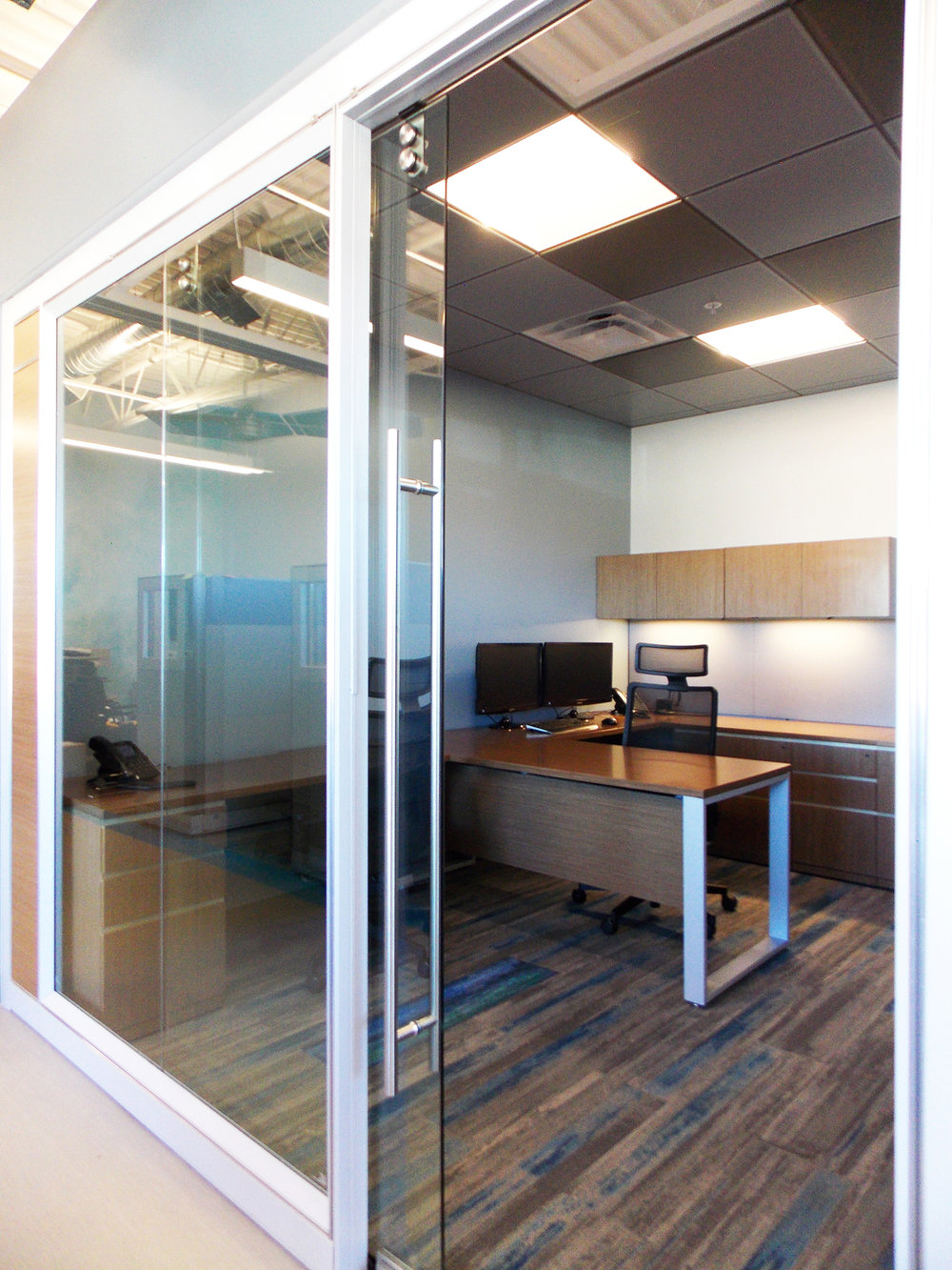 This aluminum and glass architectural wall system provided by  Office Interiors Denver  separates the private offices and conference room from the open work area and cubicles. Natural light from the storefront floods across the space into the private offices so that everyone can take full advantage of the daylight.