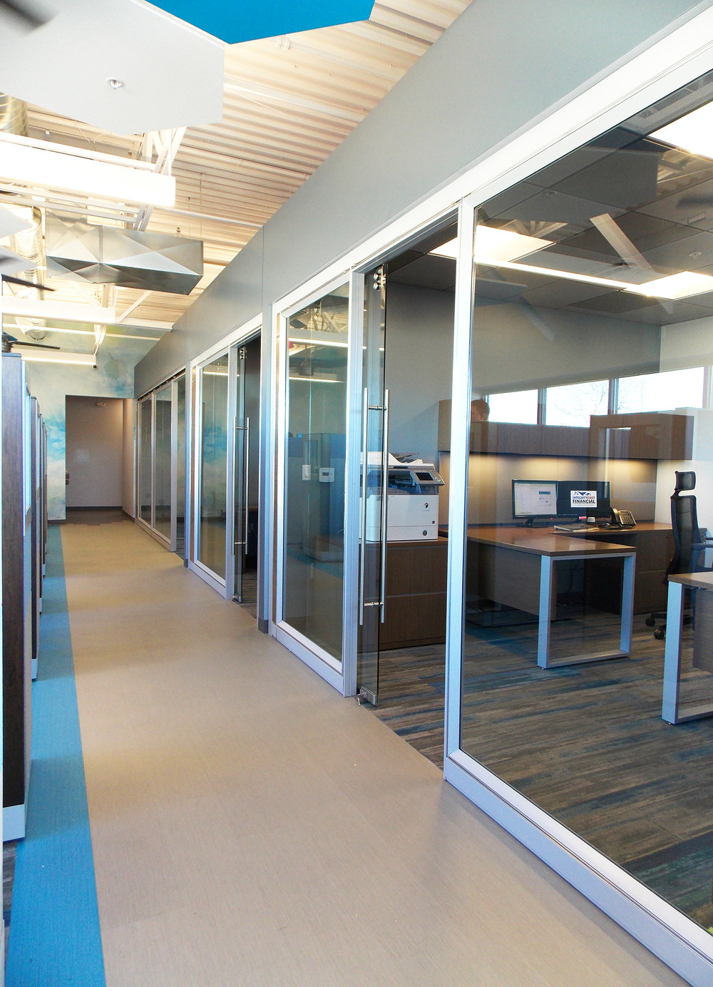 The main walkway separating the private offices from open offices area is  Patcraft's Metallix  luxury vinyl tile. Throughout the office, it changes between a mix of greys but is accented by a bright blue stripe. The  Milliken  carpet tiles are primarily grey and accented by blue, but vary in saturation whether you are in the open office or conference room.