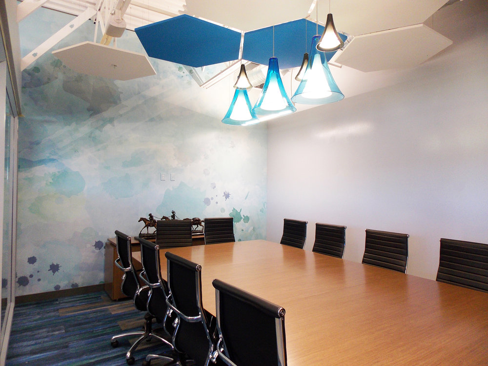 The conference room features special blown glass  Tech Lighting  fixtures clustered above the conference table for a significant impact. They are accented in place by  Armstrong Soundscapes  clouds and an original watercolor wall graphic that stretches across the back wall created by Angela Harness, one of our very own designers.