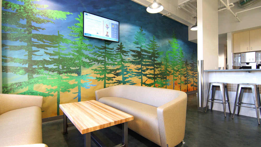 This customized, colorful wall graphic incorporates brighter colors to complement the overall color palette and help infuse a bit of stylized nature into the break room.