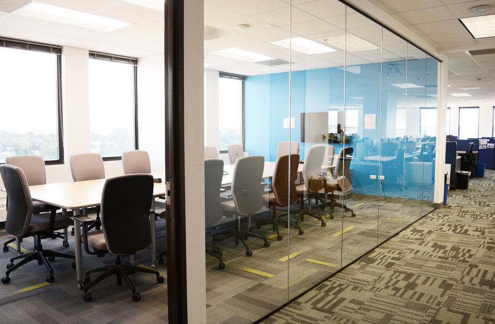 The large conference room, located along the south glass perimeter, utilizes salvaged glazing from the previous build-out to allow natural light into the space. Kestrel used two coordinating Patcraft carpet tiles to distinguish meeting space from open office.
