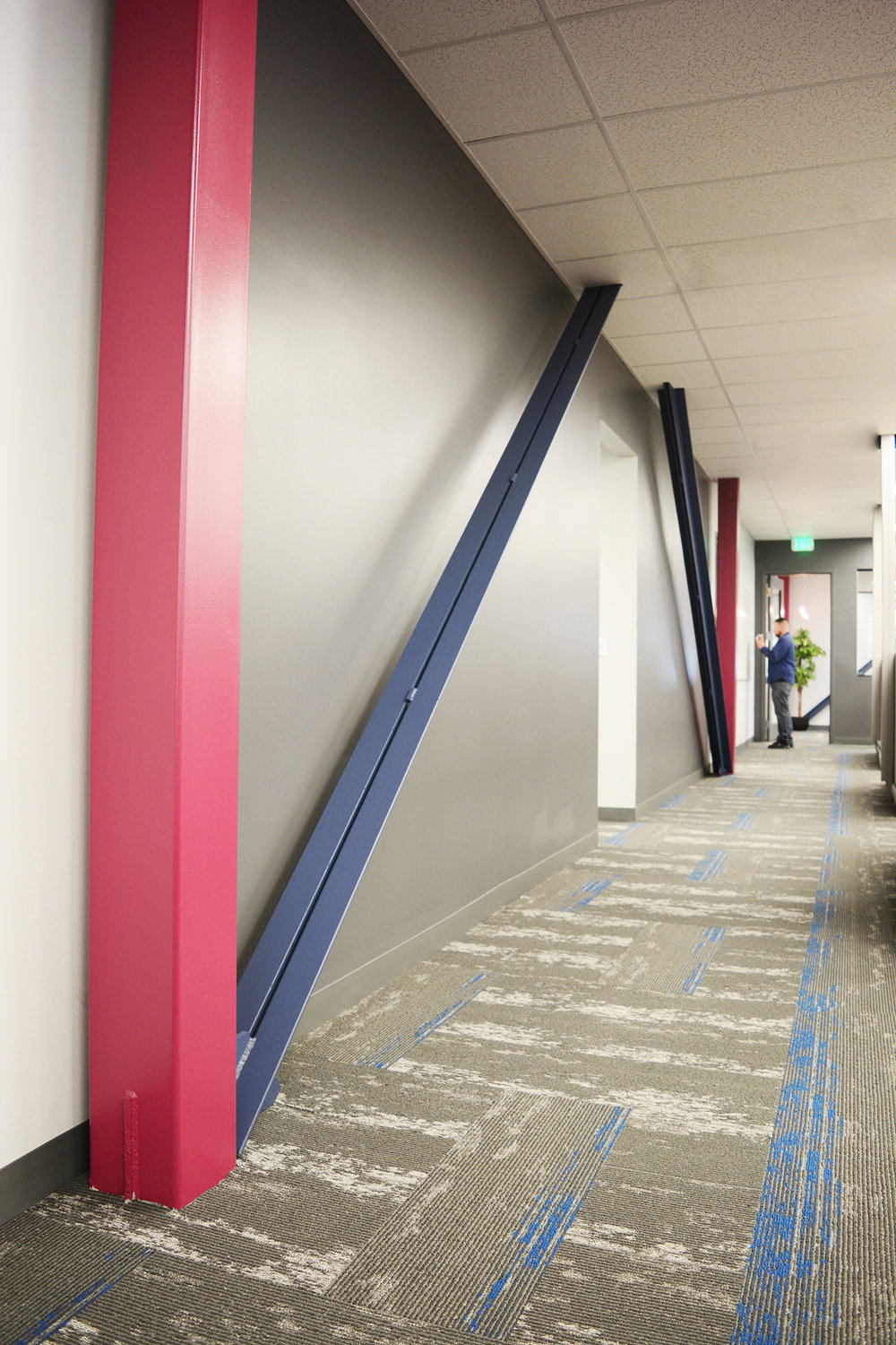 Throughout the office space structural columns and bracing were left exposed and branded with Alpha's colors. The diagonal lines of the bracing and high chroma colors created a more engaging and dynamic space.
