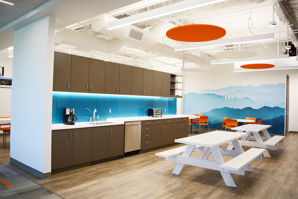 The double sided break room wall divides the space to allow for multiple zones of seating and furniture types, provided by  Officescapes . The picnic tables add a great regional touch as well as a functional aspect to the room. A large mountain scene graphic on the back wall anchors the space and adds depth, color and wonder.