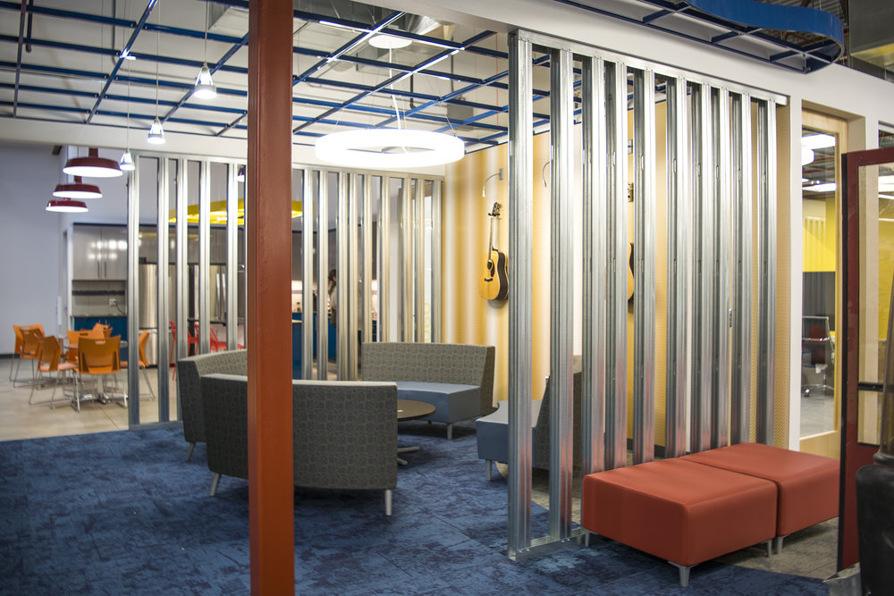 It was important for the design of the office that no space felt separated from the rest. The solution was to use  Armstrong  open colored grid to bring the ceiling level down in certain meeting areas, as well as use exposed metal stud walls that created a space barrier, but allowed for visual presence and connection.