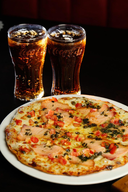 A HOUSE PUB & GRILL Su dueño Thomas Alfaro, cuenta con más de 8 años de experiencia en el mercado de bares y restaurantes; pasióndonde coinciden la producción, el servicio y la gastronomía. Alfaro, participa permanentemente en capacitaciones con otros chefs y mixólogos para mantenerse a la vanguardia en el mundo de la gastronomía. Además de A House Pub & Grill, administra un restaurante de comida mediterránea llamado La Tapería en Alajuela. La pizza fue elaborada en conjunto con el chef Ariel Rosales. #PIZZASALMONSEASON  Pizza de pasta delgada cocinada a la parrilla, sazonada con ajo y romero, cubierta con salsa bechamel, con una mezcla de quesos mozzarella y monterrey preparada en el restaurante, salmón ahumado, cubos de tomates frescos, alcaparras y pesto; logrando un excelente equilibrio de sabores ahumados, ácidos y notas frescas.