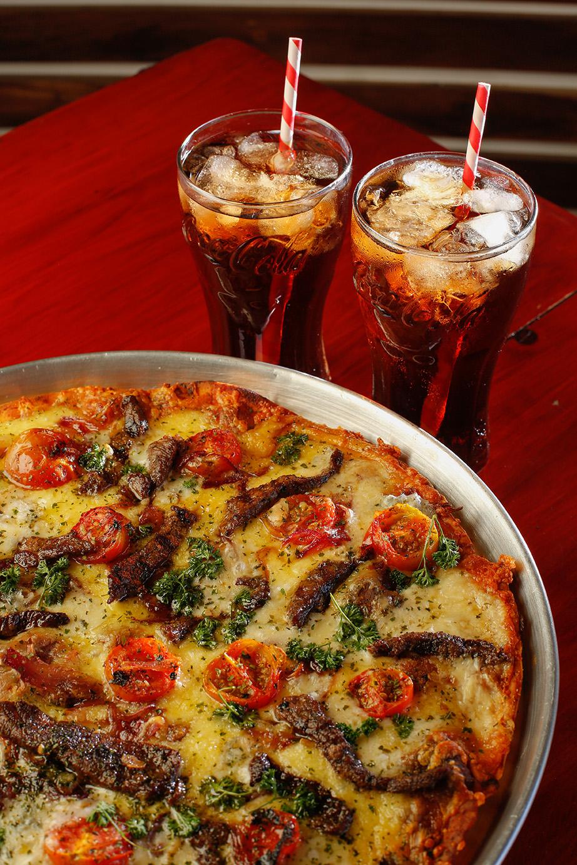 EL PORTÓN ROJO La receta surgió en una reunión de pruebas entre los dueños, Giannina Feoli, Karla Chaves y Joshua Muñoz, de la manodel pizzero principal, Jairo Campos. #PIZZADONQUICO Pizza en pasta delgada estilo siciliana con una base de salsa de tomate, queso mozzarella, lomito a la parrilla, tomates cherry, cebolla caramelizada, queso gorgonzola y perejil.