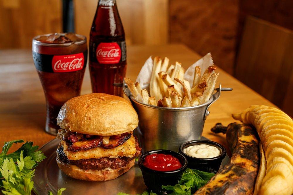 """MAD Burger and Beer   ¡MAD! Hay que estar bien loco para dejarlo todo y dedicarse a hacer la hamburguesa perfecta. Ilan se considera a si mismo más tico que el gallo pinto; por eso no sorprende encontrar dentro de sus creaciones maestras platos con ingredientes de los """"nuestros"""". Inicia su recorrido cuando viaja a Estados Unidos para certificarse como mecánico automotriz en el reconocido Universal Technical Institute, es ahí donde descubre un vacío en la gastronomía costarricense: la verdadera hamburguesa gourmet.  #AVENIDACENTRAL   Inspirada en un gran clásico del rock nacional de Inconsciente Colectivo. Manteniendo una identidad tica y fiel a sus sabores con el toque MAD. Pan brioche, torta de carne 100% de res fresca hecha a mano, queso artesanal empanizado, plátano maduro, chicharrón bites y nuestra salsa secreta ahumada."""
