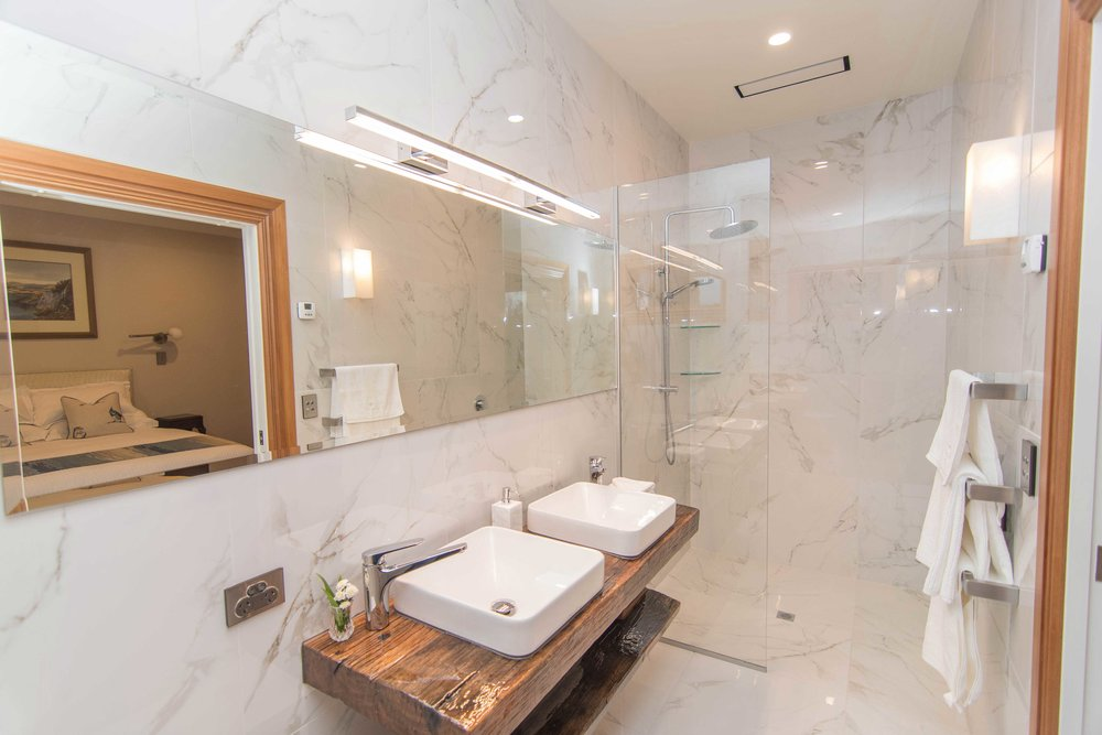 Relax and unwind in your marble-lined private ensuite bathroom.